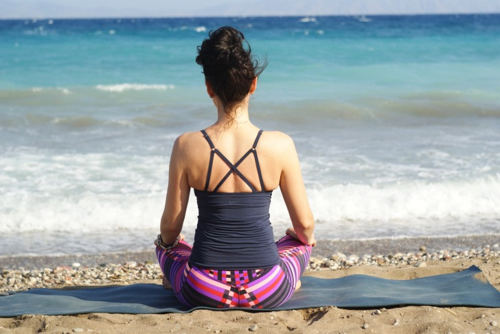 Woman looks at the sea in lotus position