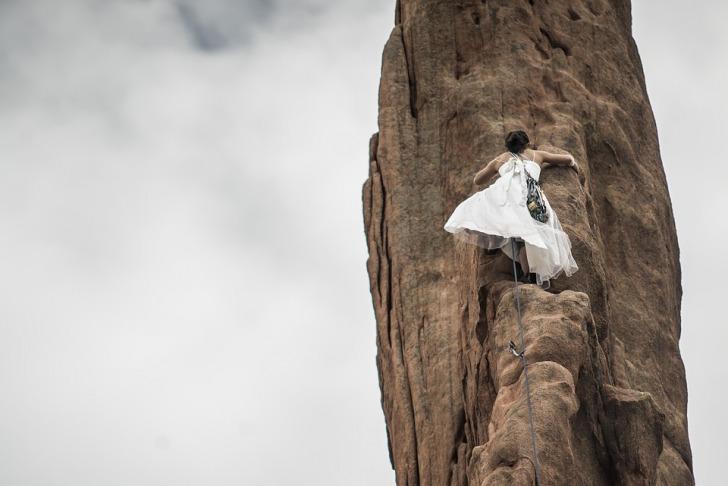 Women in white climbing a rock