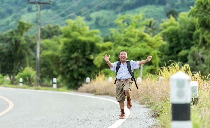 Happy schoolboy running