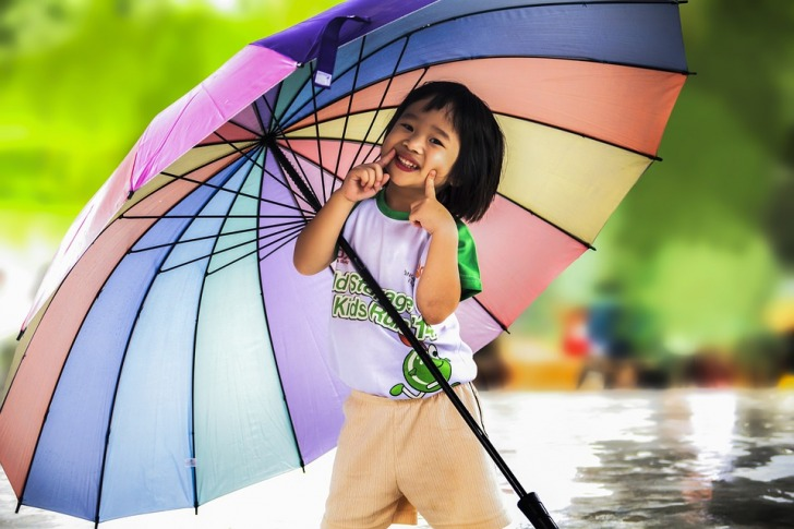 Smiling girl holding a multicolored umbrella