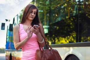 Woman with cellphone at the bus
